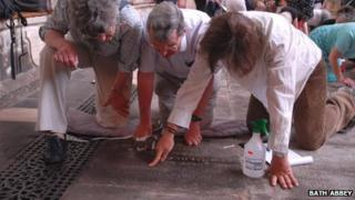 Volunteers carry out a ledger stone recording at Bath Abbey