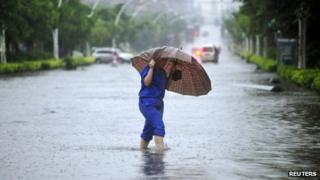 A person holding an umbrella crosses a flooded street brought about by heavy rain from Typhoon Soulik in Quanzhou, Fujian province, on 13 July, 2013