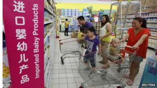 A family looks at imported milk powder products at a supermarket in Beijing, 3 July 2013