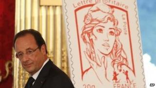 French President Francois Hollande stands next to the newly unveiled official Marianne postal stamp at the Elysee Palace (July 14, 2013)
