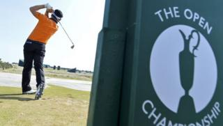 Golfer in front of open championship sign