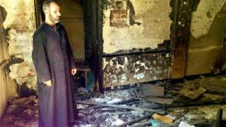 Father Ayoub Youssef in his burned-out church