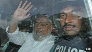 Mohammad Mujahid (L) waves from a police vehicle as he is transported to the central jail following his court verdict in Dhaka on 17 July