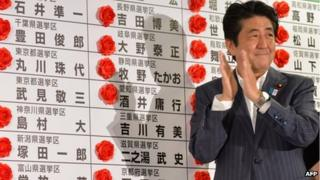 Japanese Prime Minister and President of the Liberal Democratic Party (LDP), Shinzo Abe, celebrates his party's win after he placed a red paper rose on a LDP candidate's name to indicate an election victory at the party's headquarters in Tokyo on 21 July 2013