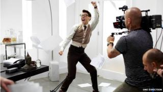 Harry from One Direction dancing in a waistcoat and glasses.