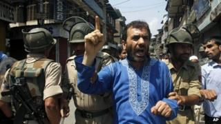 Indian policemen detain a senior leader of Jammu and Kashmir Liberation Front (JKLF) Javed Ahmad Mir during a protest against the killing of four villagers Wednesday night, in Srinagar, India, Thursday, July 18, 2013