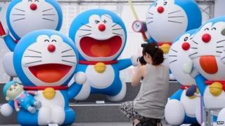 Photographer and Doraemon figures