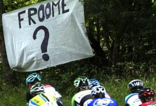 Riders go past a sign saying 'Froome?'