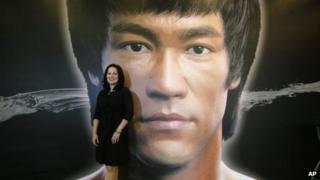 """Shannon Lee, daughter of the late Kung Fu star Bruce Lee, poses in front of a promotional poster for Lee""""s memorial exhibition at the Hong Kong Heritage Museum Thursday, July 18, 2013,"""