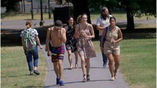 People walk in a park in central London