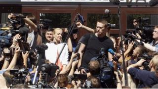 Russian opposition leader Alexei Navalny (R, centre) talks to the media, with his wife Yulia (L, centre) standing nearby, outside a court building in Kirov