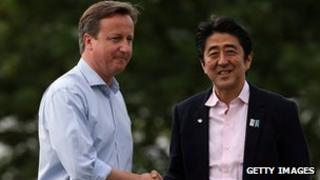 Japanese Prime Minister Shinzo Abe is greeted David Cameron at the official arrival of the G8 leaders on 17 June in Enniskillen, Northern Ireland