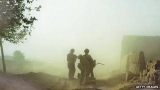 US forces are silhouetted in a dust cloud on patrol in Afghanistan