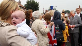Mother holding yawning baby in a queue waiting to meet Prince Charles
