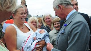 Prince Charles holding the hand of a newborn baby surrounded by a huge crowd
