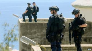 File photo: Heavily armed police from the Regional Assistance Mission to the Solomon Islands (Ramsi) stand guard on the roof of Solomon Islands parliament in Honiara 24 April 2006