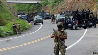 Federal agents and soldiers stand guard on a road in Michoacan after clashes with members of a drug cartel