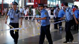 Policemen and security personnel secure Terminal 3 of the Beijing Capital International Airport where an explosion occurred on July 20, 2013
