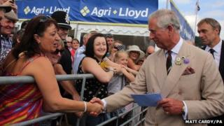 Prince Charles takes a card from Amanda Winney