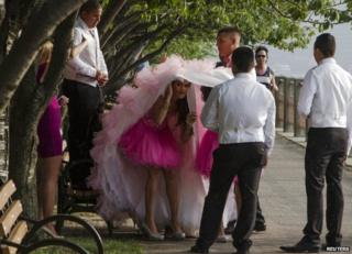 A member of a wedding party takes cover under a bride's dress on Roosevelt Island, Manhattan