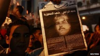 A demonstrator holds up a poster with an image of slain opposition figure Mohamed Brahmi