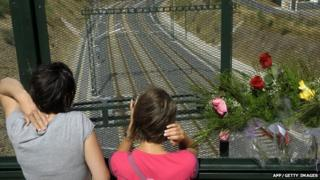 People next to flowers left for the Spain train crash victims