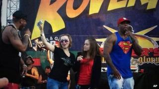 Amanda Berry, one of three women held captive in a Cleveland home for a decade, joins rapper Nelly on stage during a surprise appearance at the RoverFest concert in Cleveland