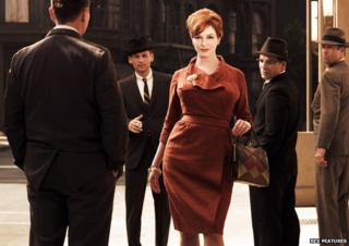 Christine Hendricks as Joan Holloway in the TV series Mad Men walking down the street with four men watching her