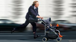 A man in a suit is running while pushing a pram with a baby inside