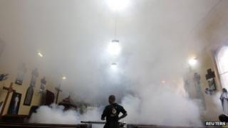 A worker fumigates in a church in Tegucigalpa on 22 June 2013