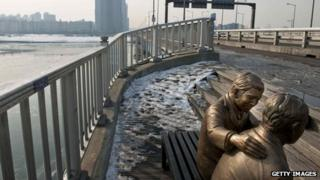 Statue (R) of a man comforting a person placed by the government to dissuade potential suicides at Mapo Bridge, over Seoul's Han river