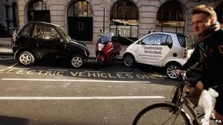 A man cycles past an electric car charging bay
