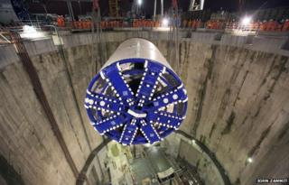 A tunnel-boring machine is lowered through a shaft on the London Crossrail site