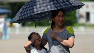 A woman and girl shelter under an umbrella against the strong sun as they walk along a street in Beijing on July 28, 2013
