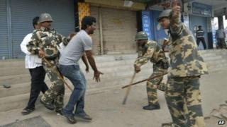 security officers use batons to charge at a man protesting against Telangana state on Wednesday, July 31, 2013