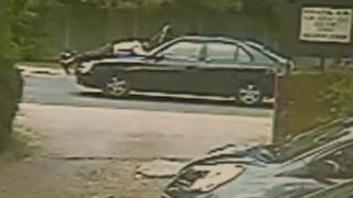 CCTV image of man on car bonnet