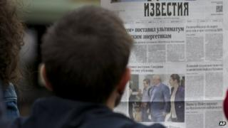 "street cafe visitor reads a fresh Russian newspaper ""Izvestia"" with a front page pictures of Russian lawyer Anatoly Kucherena, centre, and National Security Agency leaker Edward Snowden, centre left"