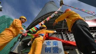 Construction workers prepare the final steel beam to be put in place a the topping out ceremony of the Shanghai Tower on 3 August 2013