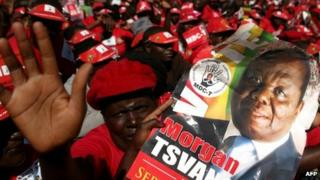 Supporters of Morgan Tsvangirai hold his portrait as they attend the final campaign rally on 29 July