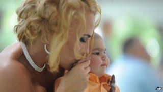 Newlywed Christine Stevenson kisses the hand of her son, Logan Stevenson, 2, after marrying Sean Stevenson