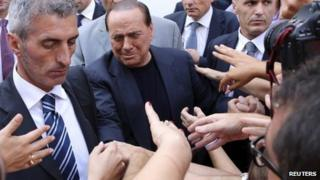 Silvio Berlusconi shakes hands with supporters at the end of a rally to protest his tax fraud conviction, outside his palace in central Rome August 4