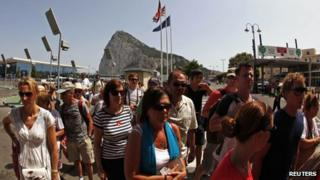 Pedestrians wait to enter to Spain at its border with the British Colony of Gibraltar in front of the Rock