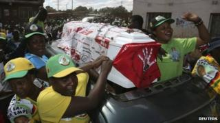 Supporters of ZANU-PF party celebrate with a coffin wrapped in a Movement for Democratic Change (MDC) flag in Mbare township, outside Harare