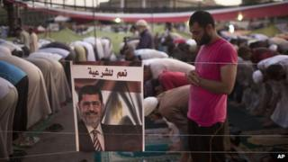Morsi supporter prays during a sit-in protest in Cairo (5 August 2013)