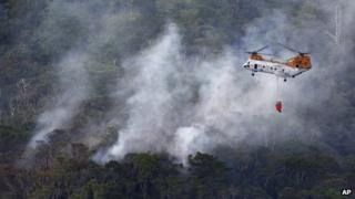 Smoke billows from the crash site of US air force rescue helicopter HH-60 at Camp Hansen as US marine helicopter CH46 flies over to extinguish the fire, in Okinawa, Japan, 5 August 2013