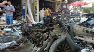 Iraqi men inspect the site of a car bomb attack in Baghdad's Karrada commercial district