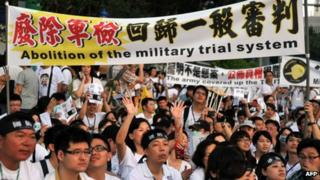 Protesters hold placards during an anti-military rally in front of Taiwan's presidential office in Taipei on 3 August 2013