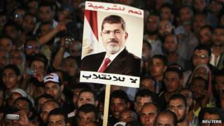 Supporters of deposed Egyptian President Mohammed Morsi hold up a poster of Morsi during a protest at the Rabaa al-Adawiya square where they are camping, in Cairo, 6 August, 2013.