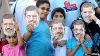 Children hold up Mohammed Morsi masks in Alexandria