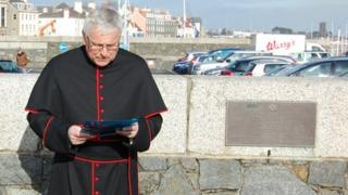 Canon Paul Mellor conducting a service on Holocaust day by the Guernsey Holocaust memorial plaque
